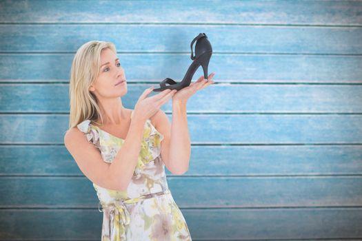 Composite image of elegant blonde admiring a shoe