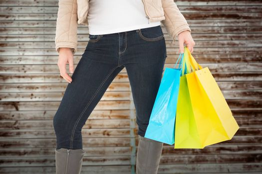 Mid section of woman holding shopping bags against wooden planks