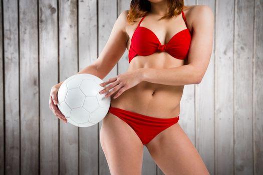 Fit girl in bikini holding football against wooden planks