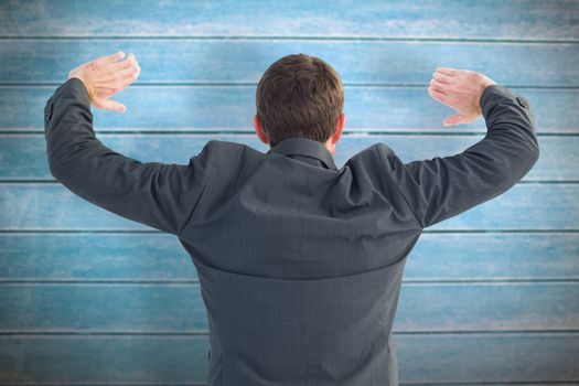 Businessman standing with hands up against wooden planks