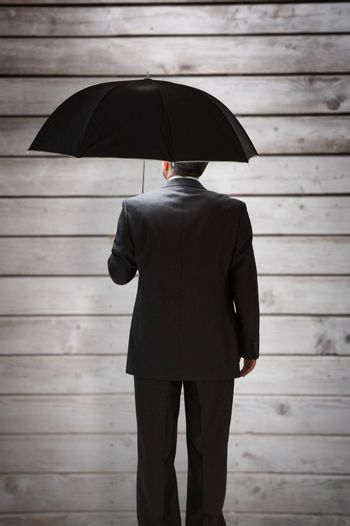 Mature businessman holding an umbrella against wooden planks