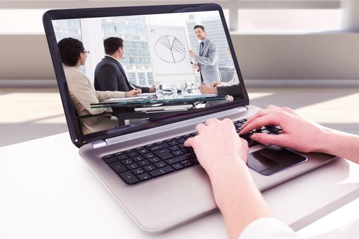 Hands typing on laptop against business people in office at presentation