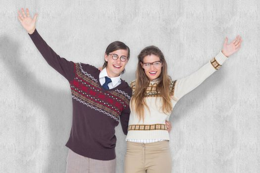 Happy geeky hipster couple embracing against white background