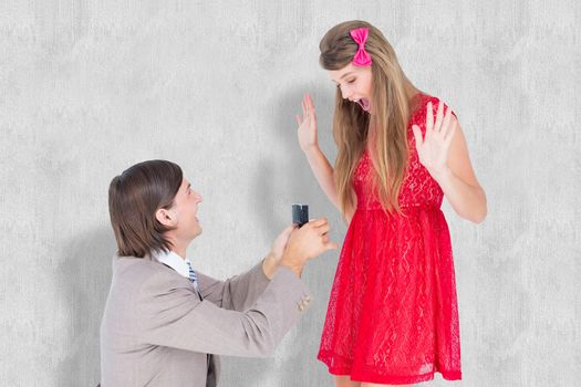 Hipster on bended knee doing a marriage proposal to his girlfriend  against white background
