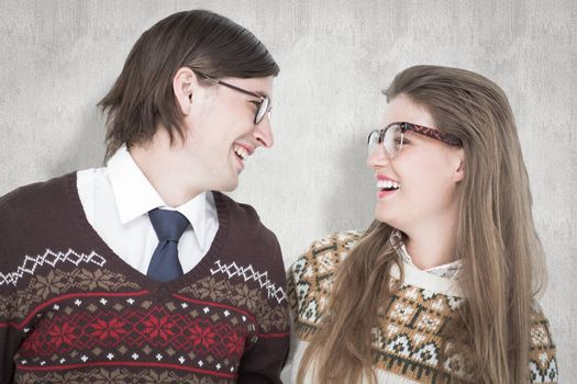 Happy geeky hipster couple looking at each other against white background