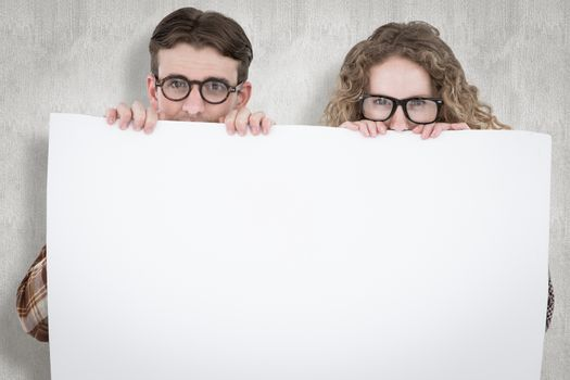 Geeky hipster couple holding poster against white background
