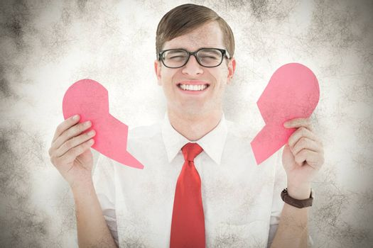 Geeky hipster holding a broken heart card against grey background