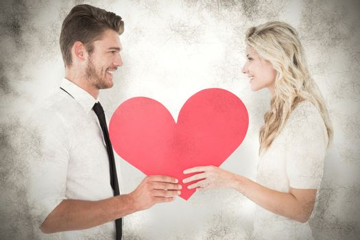 Attractive young couple holding red heart against grey background