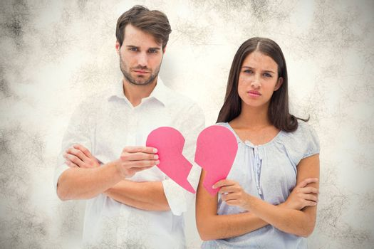 Upset couple holding two halves of broken heart against grey background