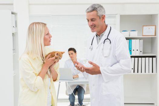 Veterinarian explaining things at cat owner in medical office