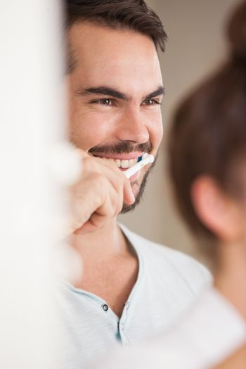 Young man brushing his teeth at home in the bathroom