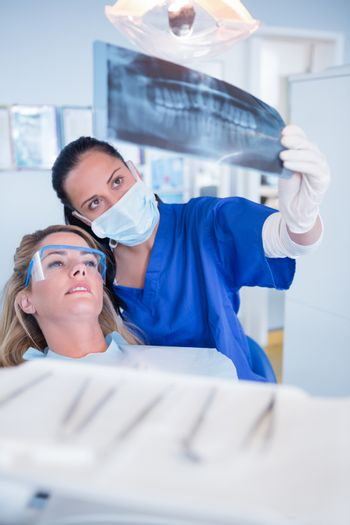 Dentist in mask explaining x-ray to patient at the dental clinic