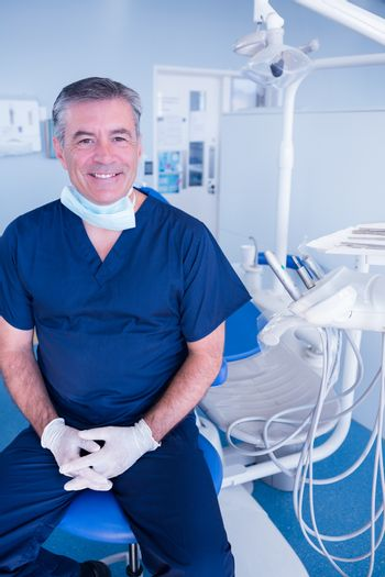 Smiling dentist in blue scrubs sitting in chair at the dental clinic