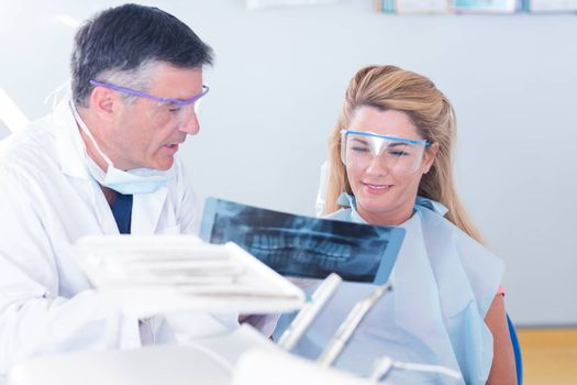 Dentist showing x-ray to his patient at the dental clinic
