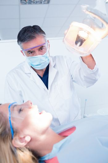 Dentist examining a patients teeth in chair under bright light at the dental clinic