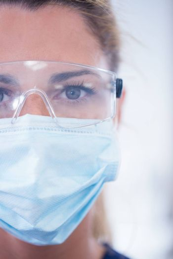 Close up of a dentist in mask looking at camera at the dental clinic