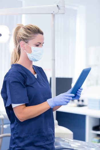 Dentist in mask and blue scrubs using her tablet at the dental clinic