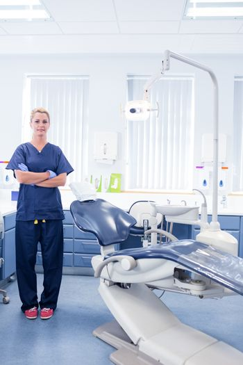 Dentist in blue scrubs standing with arms crossed at the dental clinic