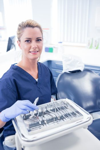 Dentist sitting with tray of tools smiling at camera at the dental clinic