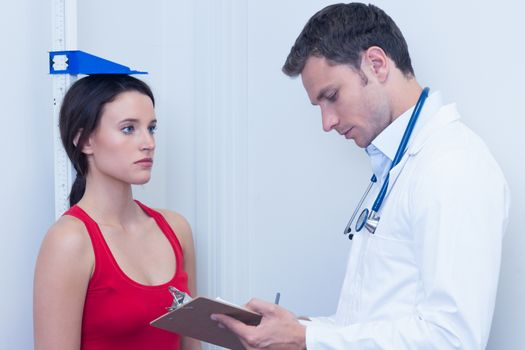 Doctor writing size of his patient on clipboard