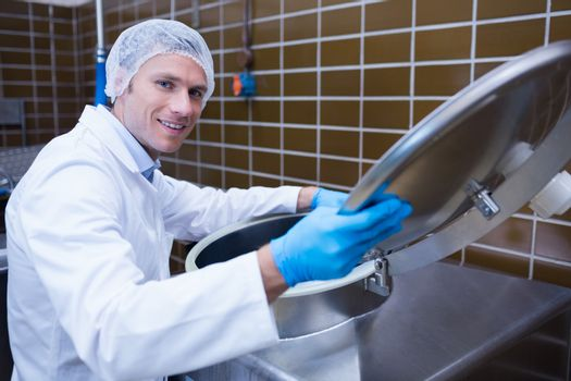 Smiling man in lab coat opening the lid of the machine