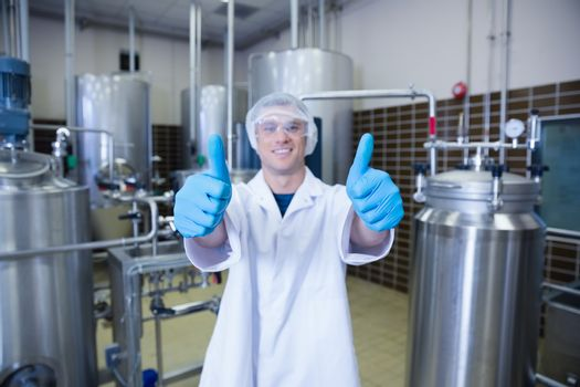 Positive man in lab coat giving thumbs up