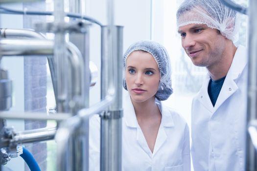 Smiling scientist with colleague looking metal gauge