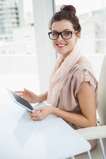Smiling causal businesswoman using tablet