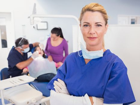 Dentist with folded arms with patient behind her
