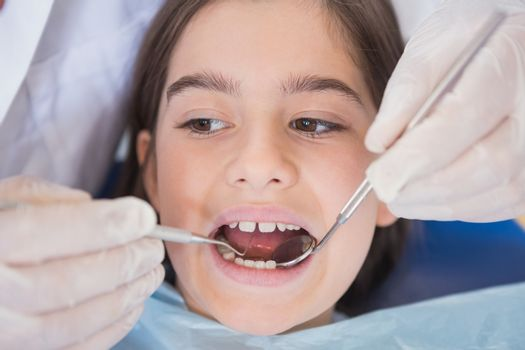 Dentist using dental explorer and angled mirror in mouth open of a patient