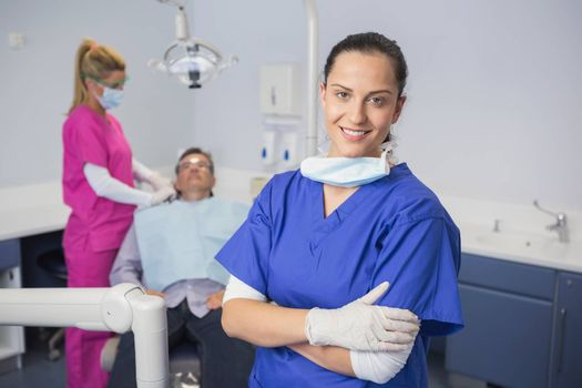 Smiling dentist with arms crossed and patient behind her