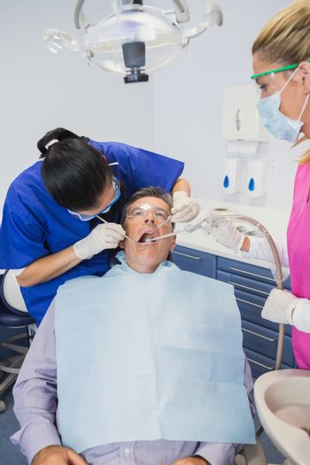 Dentist examining a patient with her dental nurse holding suction hose