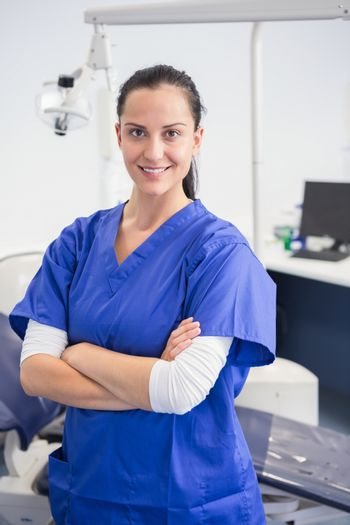 Smiling dentist with arms folded in dental clinic