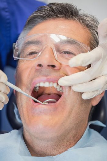 Patient mouth open and dentist examining with angled mirror in dental clinic
