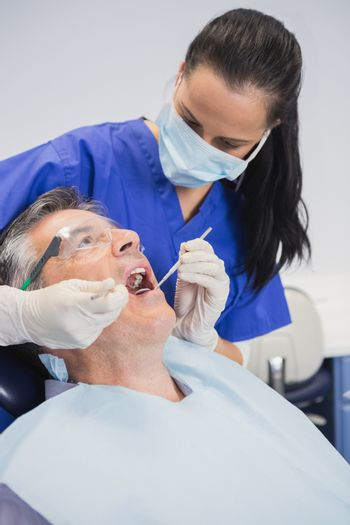 Dentist wearing surgical mask examining patient with tools