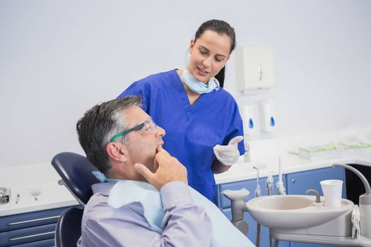 Dentist talking with her patient in dental clinic