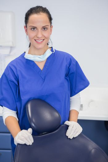 Portrait of a cheerful dentist behind a dentists chair in dental clinic