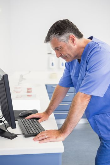 Dentist concentrated about computer monitor in dental clinic