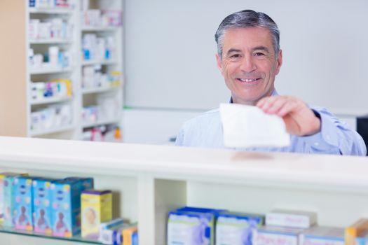 Pharmacist with grey hair holding a prescription