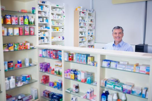 Pharmacist with grey hair standing behind shelves of drugs