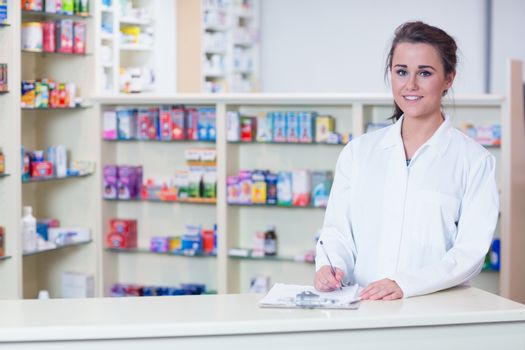 Smiling trainee in lab coat writing a prescription