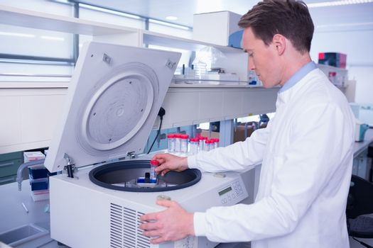 Chemist in lab coat using a centrifuge