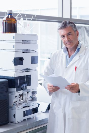 Scientist standing in lab coat holding a document