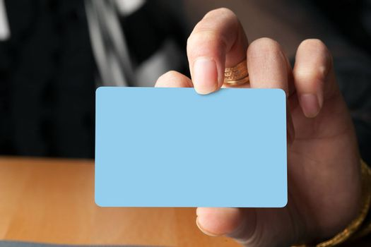 Female hand holding a blank business card gift card or credit card.  Plenty of copyspace for your logo or design.