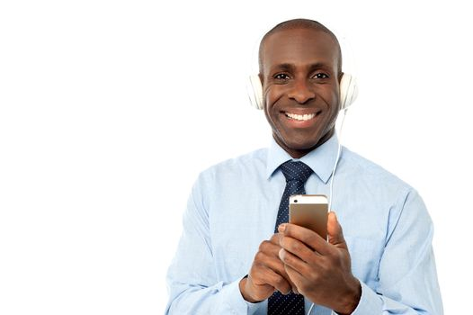 Cool young businessman enjoying music