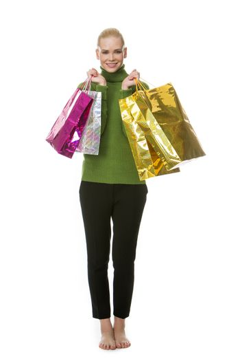 blonde smiling woman carrying gift bags and looking at the camera