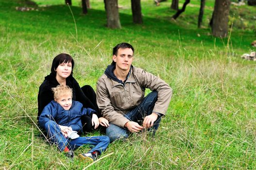 family with funny son in the forest during early autumn