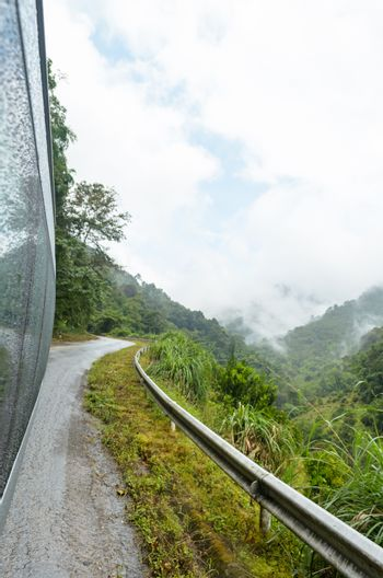 Travel with a van on road in the forest and mountain amidst morning fog of Thailand