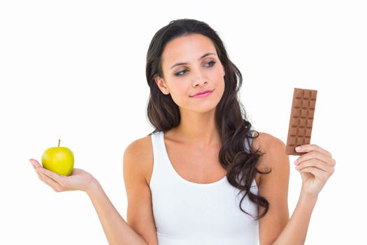 Pretty brunette deciding between apple and chocolate
