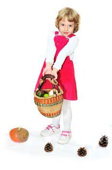 little girl standing with basket full of vegetables